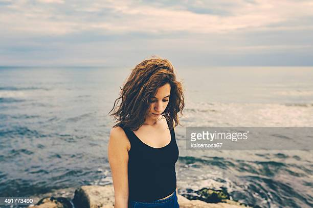 Pensive girl standing on a pier