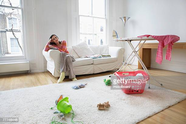 Pensive Housewife in Messy Living Room