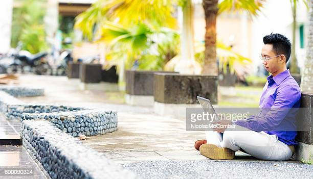 Pensive Indonesian male student sitting outdoors with laptop
