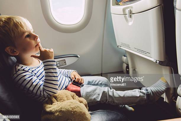 Pensive little boy sitting on an airplane