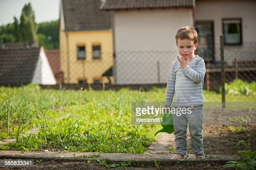 Pensive little boy standing in the garden with childrens watering can
