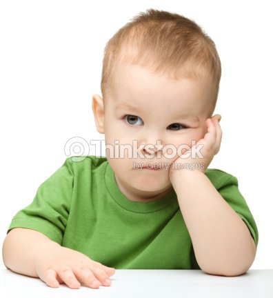 Pensive little boy support his head with hand : Stock Photo