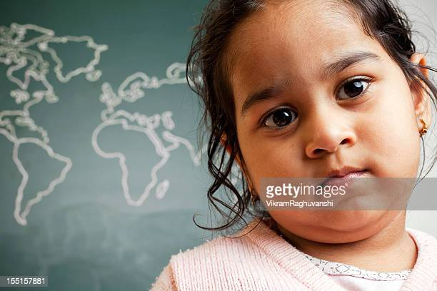 Pensive Little Indian Preschool Girl in Front of World Map