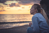 Pensive lonely smiling young woman looking with hope into horizon during sunset at beach