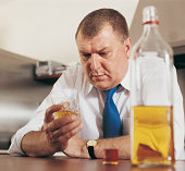 Pensive Man Holding a Glass of Whisky