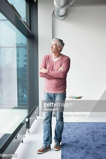 Pensive man looking through window