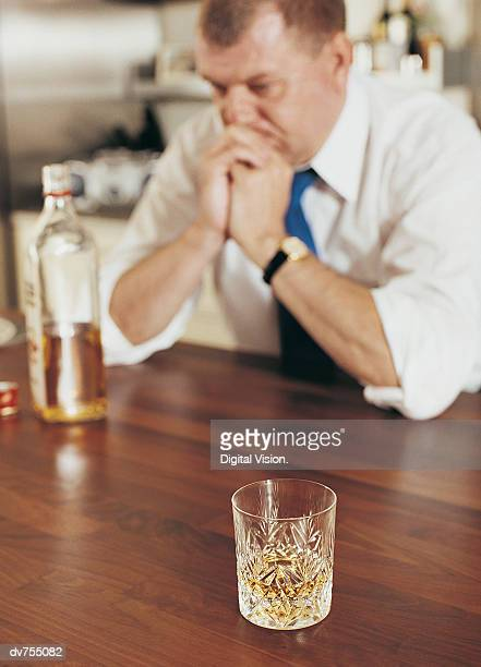 Pensive Man Sitting at a Table With a Glass of Whisky