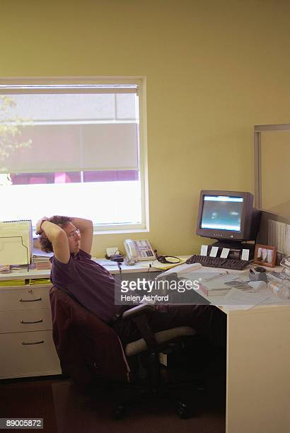 Pensive man sitting at desk in office