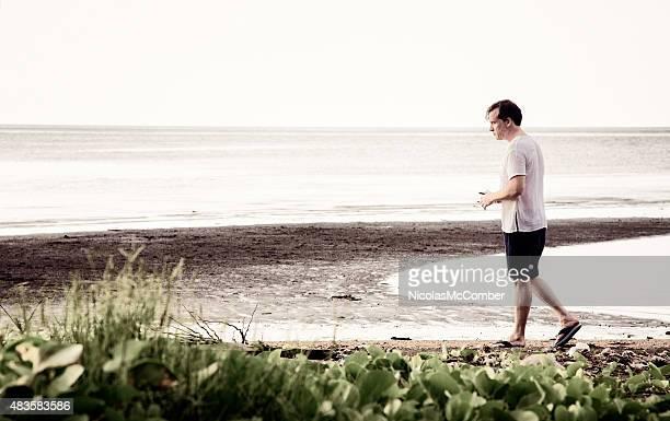 Nachdenklicher Mann geht auf verseucht beach mit traurigen Ausdruck