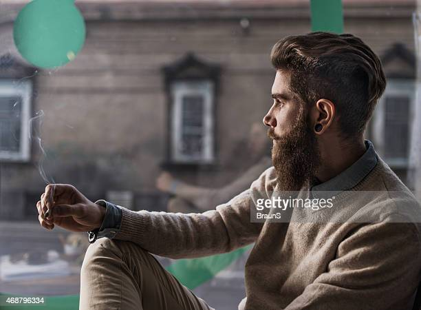 Pensive man with a cigarette looking through window.