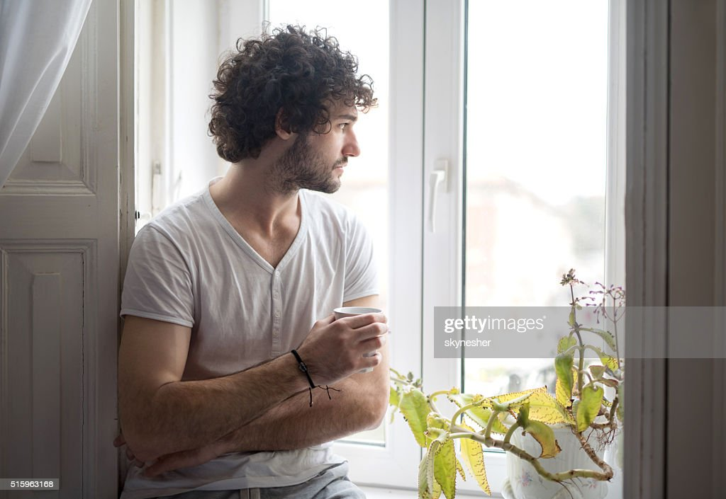 Pensive man with coffee cup looking through the window. : Stockfoto