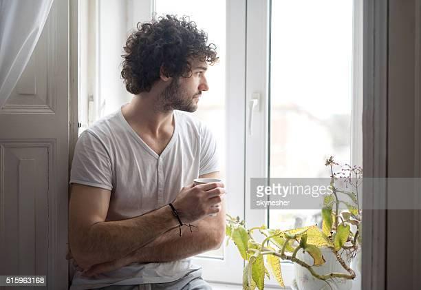 Homem pensativo com copos de café, olhando através da janela.