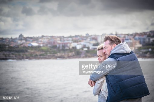 Pensive mature adult couple embracing and looking out to sea