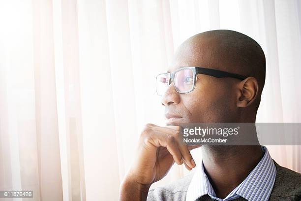 Pensive mature bald black man by a window