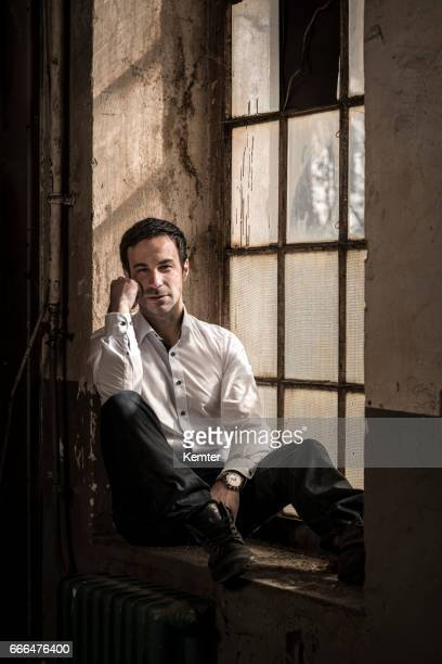 pensive mature man sitting at old window