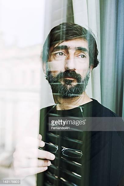 Pensativo de meia idade homem Olhando através de uma janela