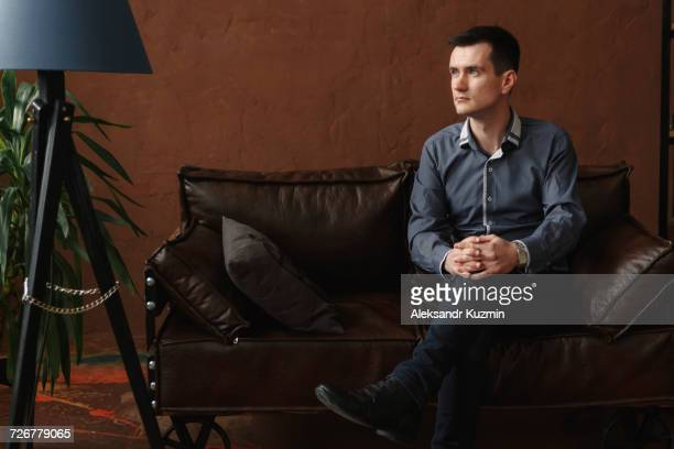 Pensive Middle Eastern man sitting on sofa