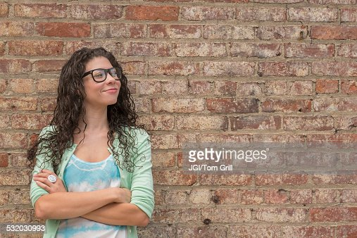 Pensive mixed race woman standing with arms crossed