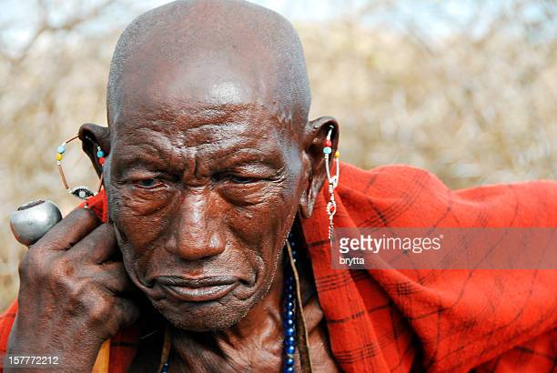 Pensive old African Masai warrior with pipe and jewelry, Tanzania