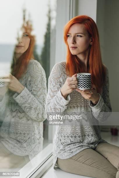 Femme rousse songeur boire du café par la fenêtre.