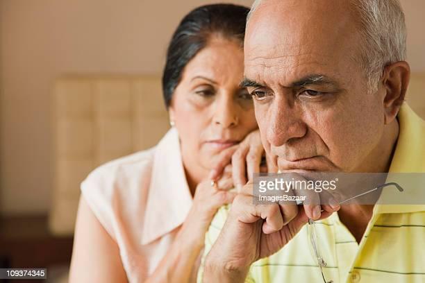 Pensive senior couple indoors