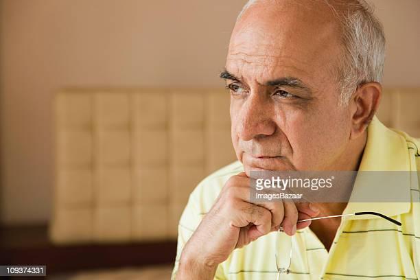 Pensive senior man, holding glasses indoors