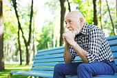 Thoughtful senior man outdoors. Elderly man in casual sitting on the bench in sunny park, copy space