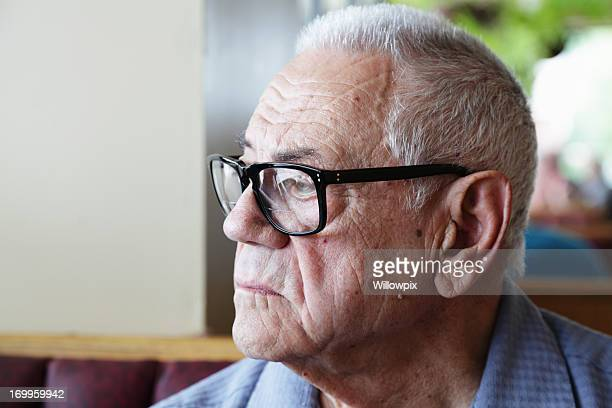 Pensive Senior Man Sitting Alone and Looking Out Window