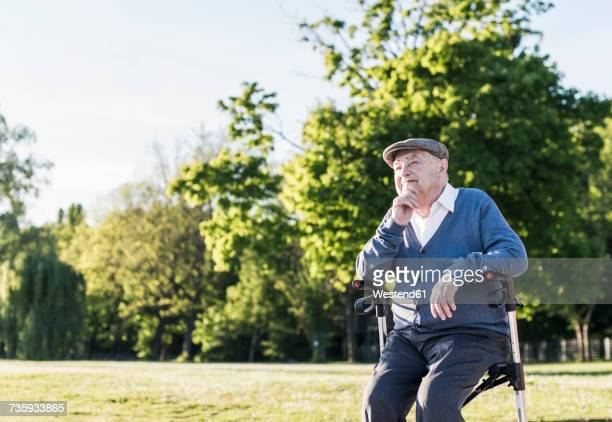 Pensive senior man sitting on his wheeled walker in nature