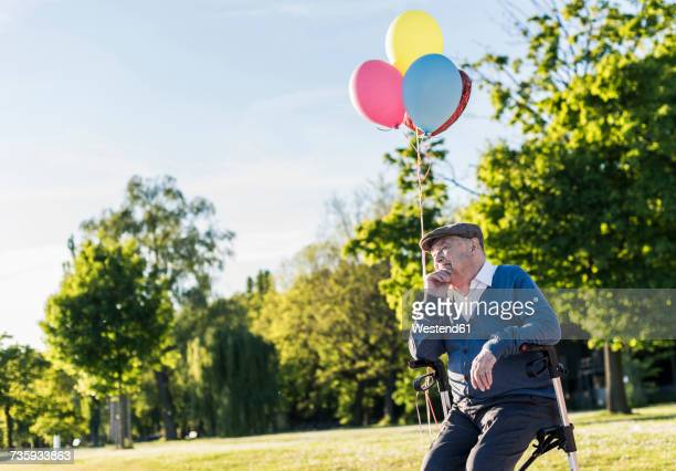 Pensive senior man with balloons sitting on his wheeled walker in nature