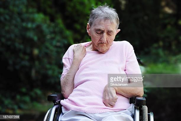 pensive senior woman in wheelchair