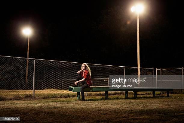 Pensive teenage girl sitting on bleachers at night