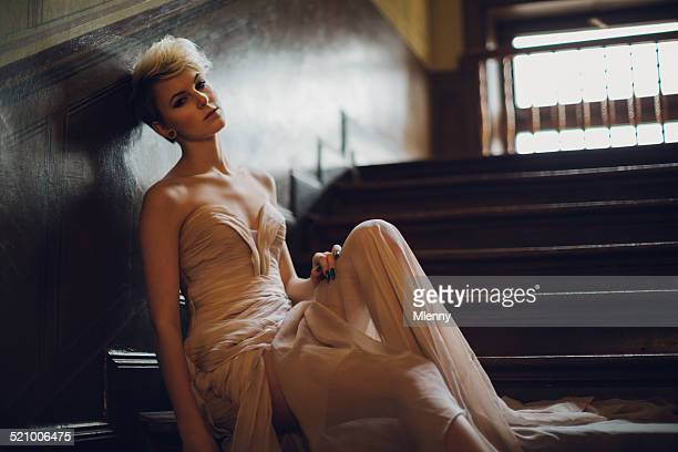 Pensive woman in evening gown sitting on stairway