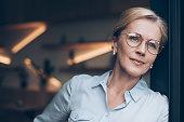 portrait of pensive woman in eyeglasses looking away