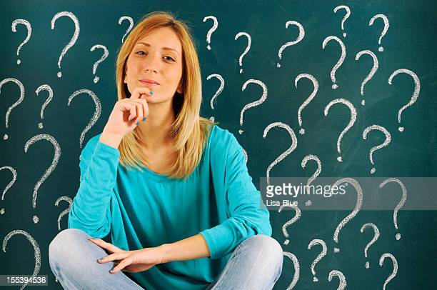 Pensive Woman in front of Question Marks Sketched on Blackboard