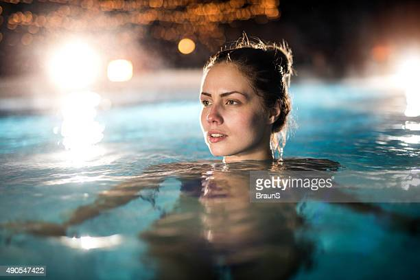 Pensive woman in the heated swimming pool outdoors.