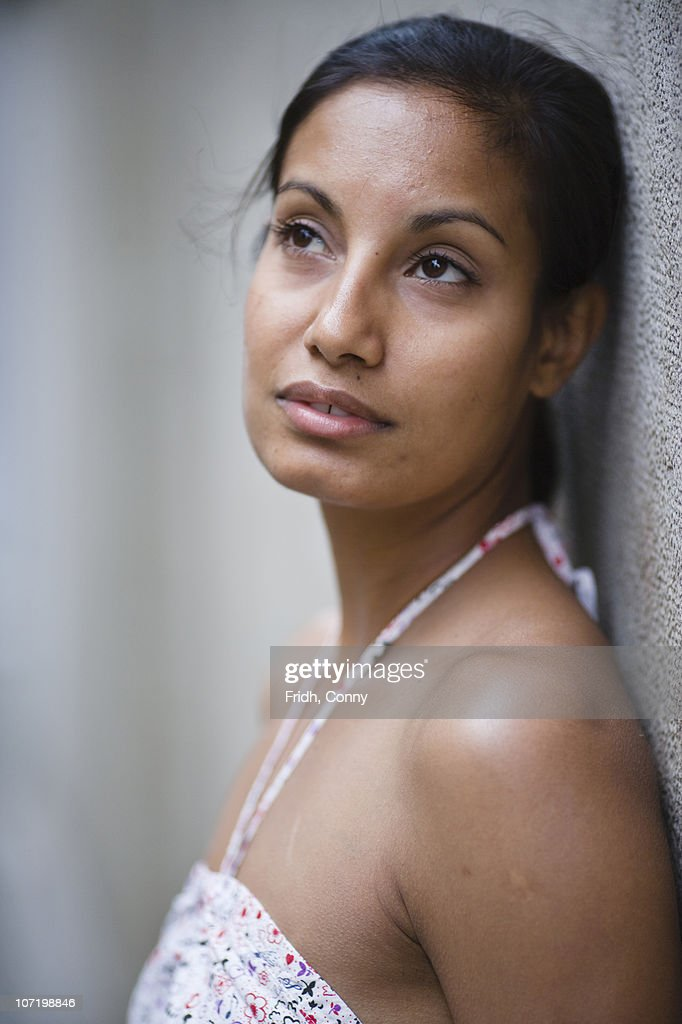 Pensive woman leaning against wall : Stock Photo