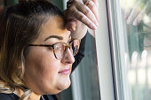 pensive caucasian overweight woman looking through a window