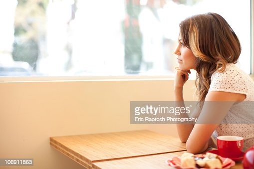 Pensive woman looking out window
