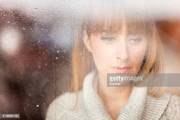 Pensive woman looking through window on rainy day