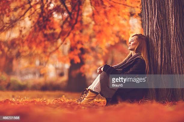Nachdenklich Frau sitzt in der Natur und Wegsehen.