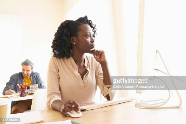 Pensive woman using computer and thinking