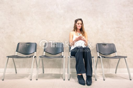 Pensive woman with mobile smart phone sitting in waiting room : Stock Photo