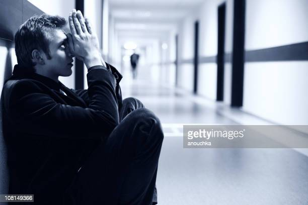 Pensive Young Businessman Sitting in Hallway