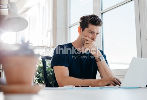 Pensive young male executive using laptop at his desk : Stock Photo