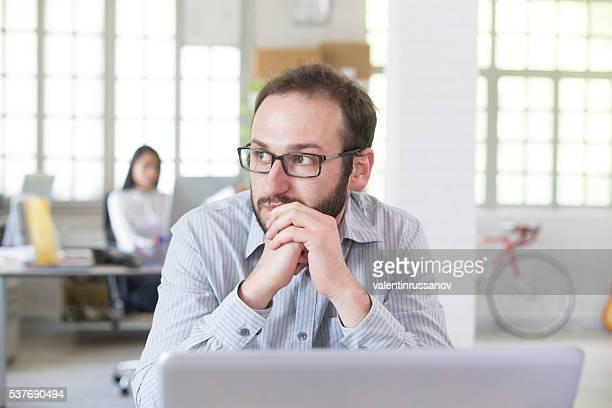 Pensive young man with eyeglasses at the office