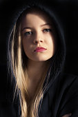pensive young woman in black hood on black background