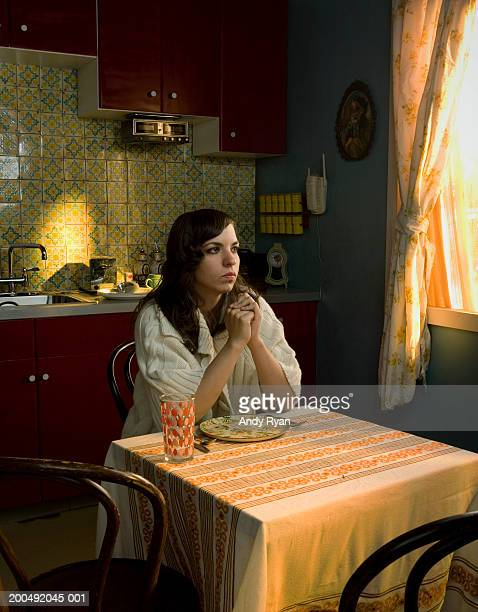 Pensive young woman sitting at kitchen table with empty plate