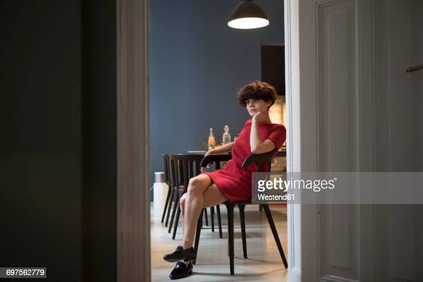 Pensive young woman sitting in the kitchen