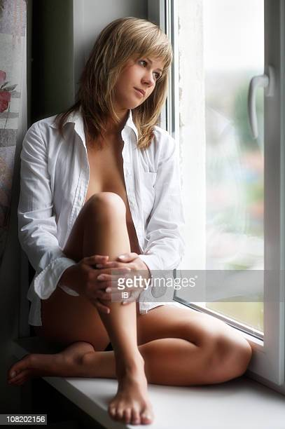 Pensive Young Woman Sitting on Window Sill